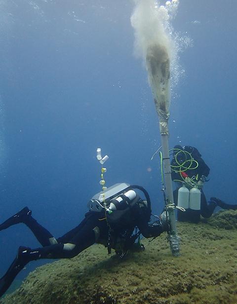 Plongeurs manipulant l'aspirateur sous-marin